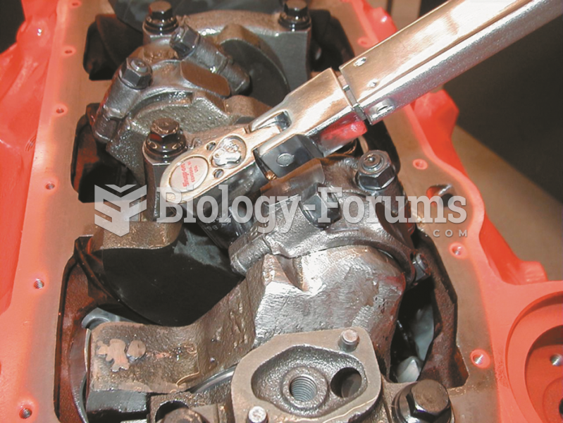 Using a torque wrench to tighten connecting rod nuts on an engine.