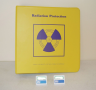 Radioactive protection services record book and two badge-style dosimeters.