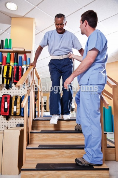 A medical assistant helps a patient walk with a gait belt.
