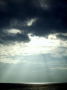 Sunlight shining through clouds, giving rise to crepuscular rays.